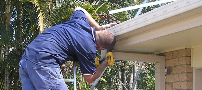 man repairing gutters on the edge of the roof