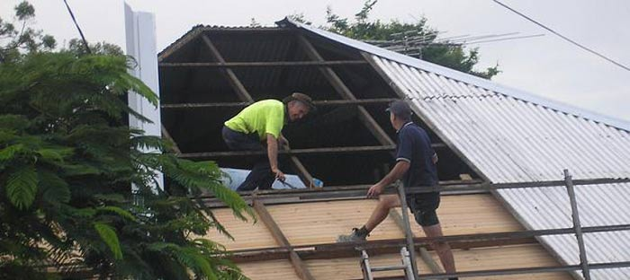 two men working on roof restoration inside of a Brisbane home's roof