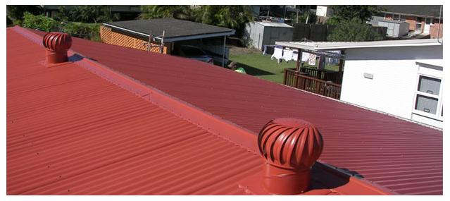 two red whirlybirds on a red metal roof